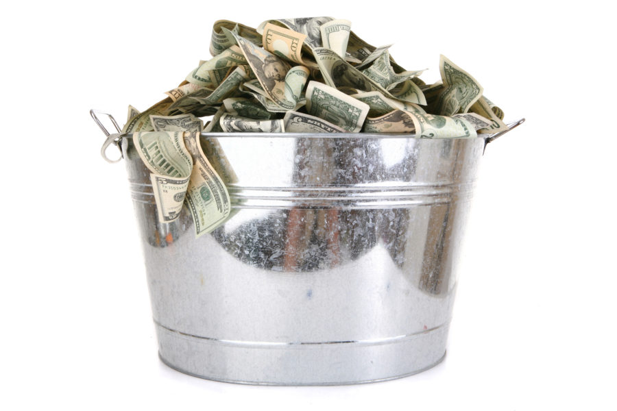Stock photo of a metal bucket filled with paper money