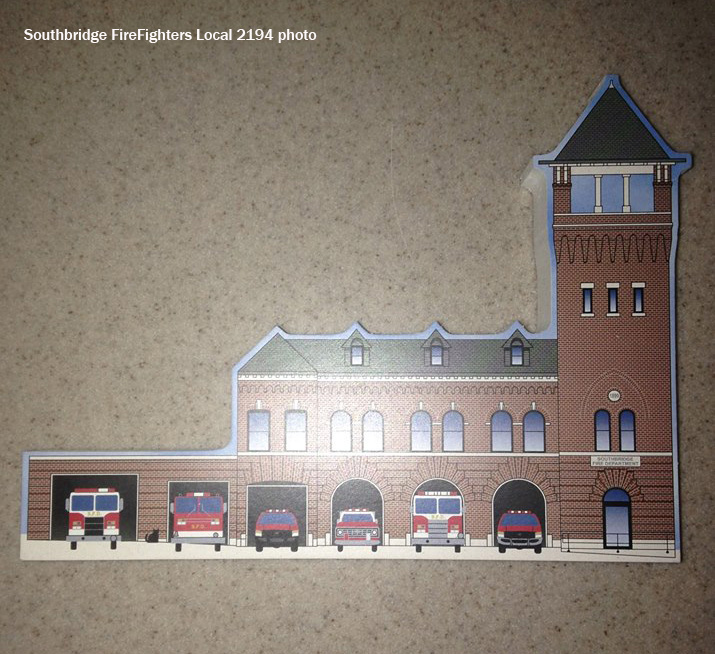 Firefighters selling wooden cutouts of historic firehouse